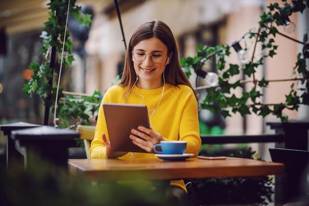 Jonge lachende freelancer zittend op het terras van café en voorbereiding op telefonische vergadering met een baas.