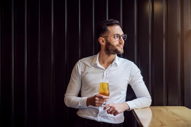 Jonge lachende geeky zakenman leunend op de tafel naast het raam en kijkt er doorheen, houdt een glas bier vast en ontspant na het werk.