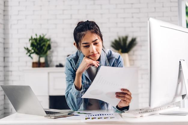 Jonge lachende gelukkig aziatische vrouw ontspannen met behulp van laptop computer werken en videoconferentievergadering online chat