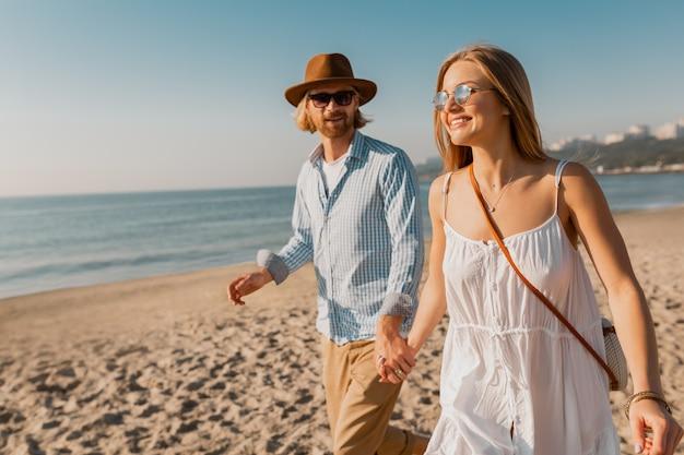 Jonge lachende gelukkig man in hoed en blonde vrouw loopt samen op het strand op zomervakantie reizen