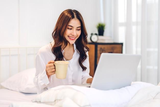 Jonge lachende gelukkig mooie aziatische vrouw ontspannen met behulp van laptopcomputer en koffie drinken in de slaapkamer thuis.