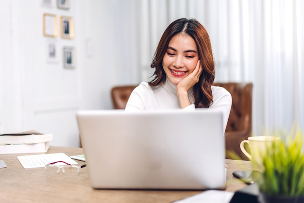 Jonge lachende gelukkig mooie aziatische vrouw ontspannen met behulp van laptopcomputer in de kamer thuis. jonge creatieve meisje werken en typen op keyboard.work vanuit huis concept