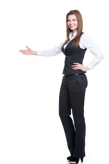 Jonge lachende gelukkige vrouw in grijs pak wijzend op iets met de hand. geïsoleerd op een witte muur.