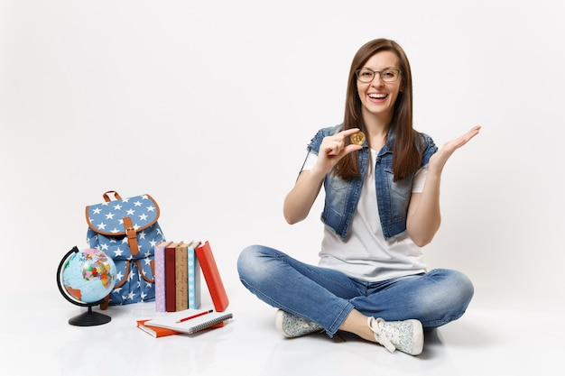 Jonge lachende gelukkige vrouw student in glazen met bitcoin verspreidende handen zitten in de buurt van globe, rugzak, schoolboeken geïsoleerd
