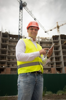 Jonge lachende ingenieur met behulp van digitale tablet op bouwplaats
