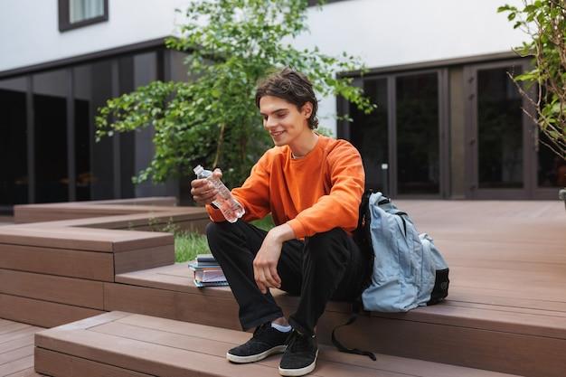 Jonge lachende jongen zit met fles water in handen en grote rugzak in de buurt van tijd doorbrengen op de binnenplaats van de universiteit