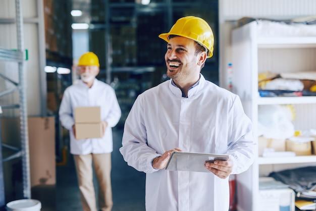 Jonge lachende kaukasische magazijnmedewerker in witte uniforme en gele helm op hoofd met behulp van tablet.