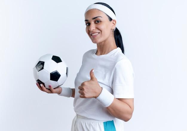 Jonge lachende kaukasische sportieve vrouw met hoofdband en polsbandjes houdt bal en duimen omhoog staande zijwaarts geïsoleerd op witte ruimte met kopie ruimte