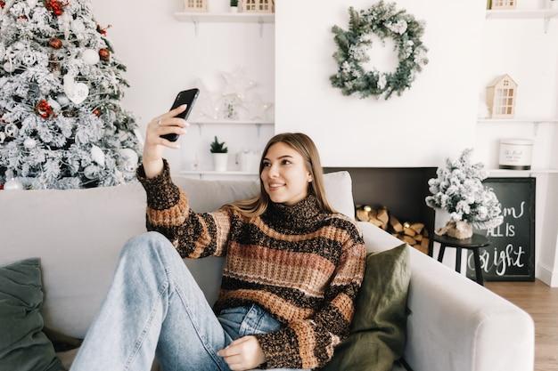 Jonge lachende kaukasische vrouw selfie met behulp van mobiele telefoon in de buurt van de kerstboom thuis.