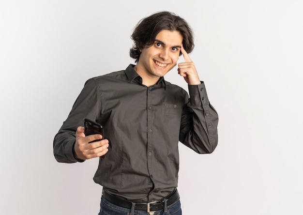 Jonge lachende knappe blanke man houdt telefoon en legt vinger op hoofd geïsoleerd op een witte achtergrond met kopie ruimte