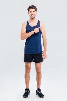 Jonge lachende knappe sportman wijzende vinger naar copyspace geïsoleerd op een grijze achtergrond
