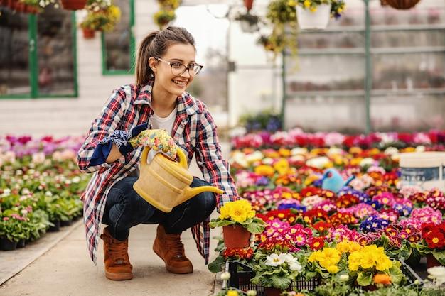 Jonge lachende kwekerij vrouwelijke werknemer gehurkt en bloemen in potten water geven.