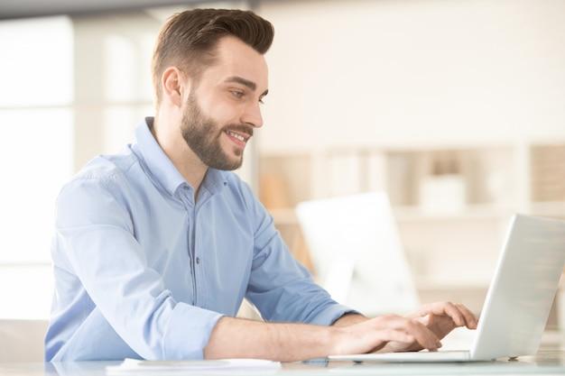 Jonge lachende makelaar in blauw shirt typen op laptop toetsenbord en kijken naar display tijdens het analyseren van online gegevens