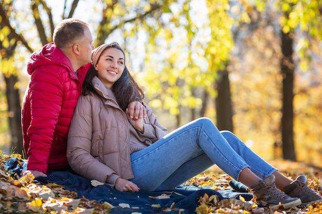 Jonge lachende man en vrouw knuffelen in het herfstpark. romantisch paar op een date. liefde en tederheid in een relatie. detailopname.