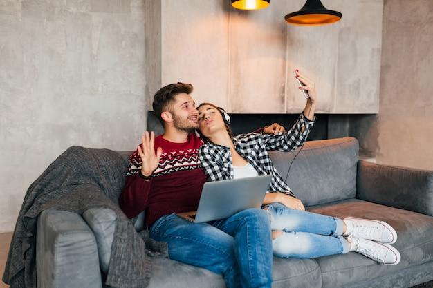 Jonge lachende man en vrouw om thuis te zitten in de winter, bezig met laptop, smartphone houden, luisteren naar koptelefoon, koppel op vrije tijd online, freelancer, dating