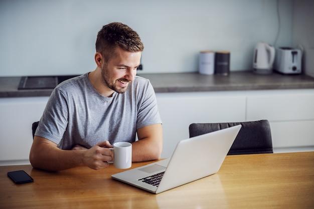 Jonge lachende man gekleed casual zittend aan de eettafel, mok met koffie in de ochtend te houden en laptop te kijken. hij bezoekt sites voor online dating.