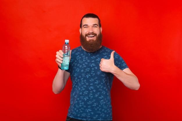 Jonge lachende man houdt en toont een fles water en duim omhoog.