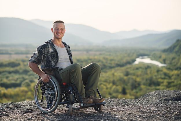 Jonge lachende man in rolstoel genieten van natuurschoon op de bergen