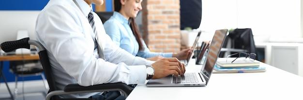 Jonge lachende man in rolstoel werkt op laptop in kantoor met vrouw collega