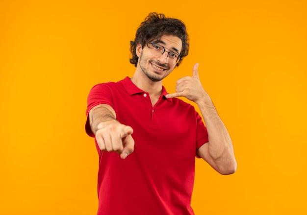 Jonge lachende man in rood shirt met optische bril gebaren bel me en punten geïsoleerd op oranje muur