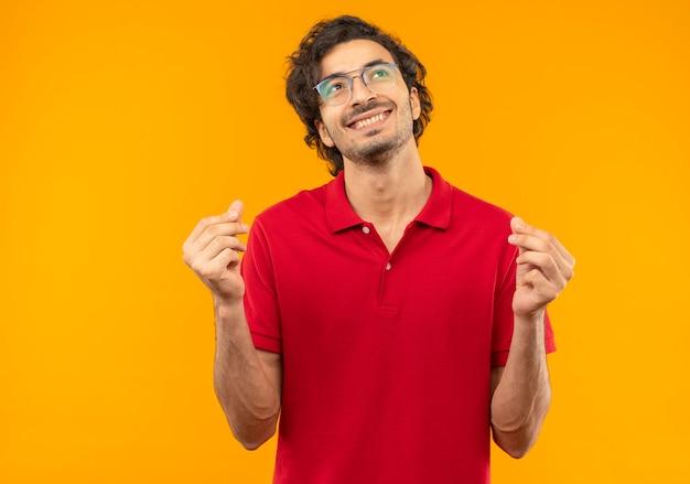Jonge lachende man in rood shirt met optische bril gebaren geld met handen geïsoleerd op oranje muur
