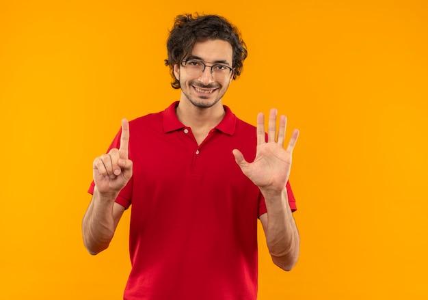 Jonge lachende man in rood shirt met optische bril gebaren zes met vingers geïsoleerd op oranje muur