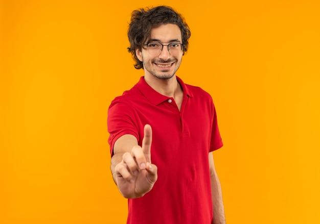 Jonge lachende man in rood shirt met optische glazen gebaren een geïsoleerd op oranje muur