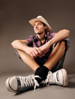 Jonge lachende man in sneakers en hoed zittend tegen een bruine achtergrond