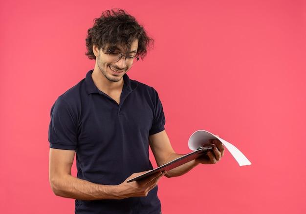 Jonge lachende man in zwart shirt met optische bril houdt en kijkt naar klembord geïsoleerd op roze muur