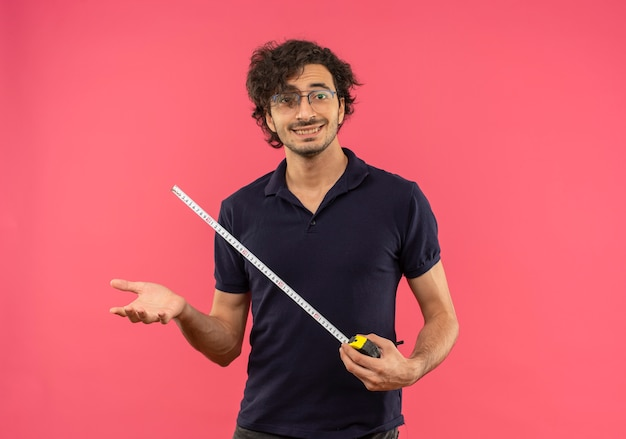 Jonge lachende man in zwart shirt met optische bril houdt meetlint geïsoleerd op roze muur