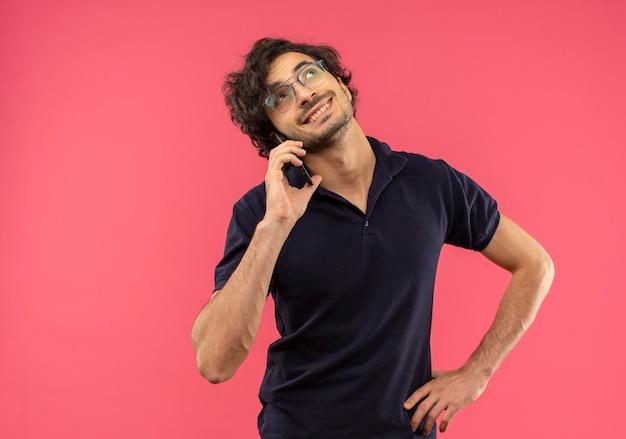 Jonge lachende man in zwart shirt met optische bril praat over telefoon en legt hand op taille geïsoleerd op roze muur