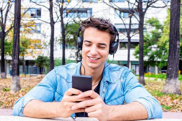 Jonge lachende man kijkt naar smartphone met koptelefoon op zijn hoofd