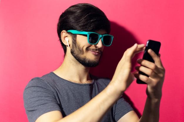 Jonge lachende man met behulp van smartphone en draadloze koptelefoon, cyaan zonnebril dragen, op roze koraal muur.