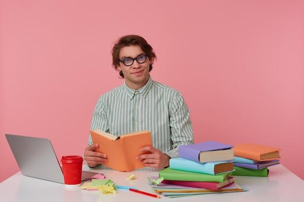Jonge lachende man met bril draagt in shirt, student zit bij de tafel en werkt met laptop, voorbereid voor examen, boek leest, ziet er vrolijk uit en geniet van het lezen, geïsoleerd op roze achtergrond.