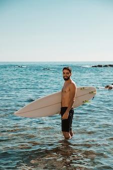 Jonge lachende man met surfplank in de buurt van strand in water