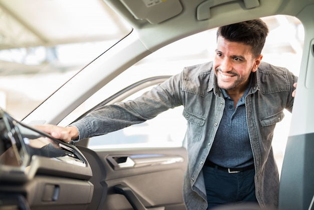Jonge lachende man nemen van het nemen van kijken naar de auto in de showroom