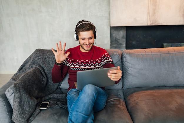 Jonge lachende man om thuis te zitten in de winter, zwaaiende hand, dragen rode trui, bezig met laptop, freelancer, koptelefoon luisteren, student online studeren