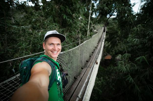 Jonge lachende man op de hangbrug selfie te nemen over de achtergrond van de grote natuur. concept van avontuur en reizen.