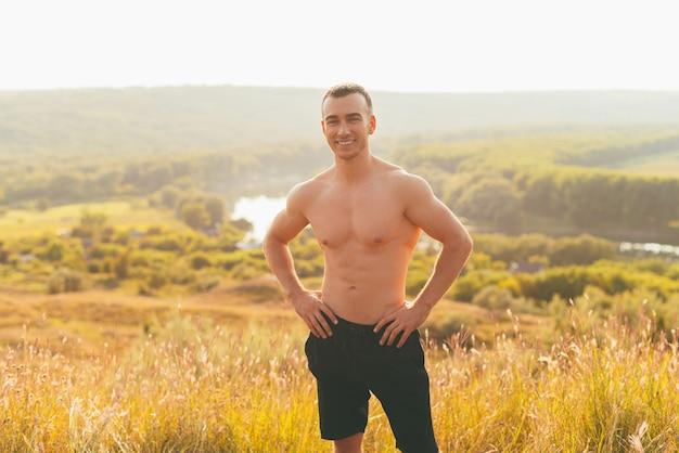 Jonge lachende man poseert na een training die buiten is gemaakt.
