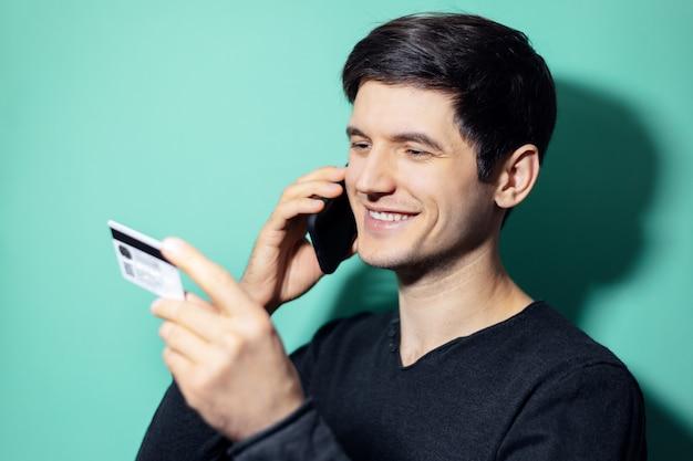 Jonge lachende man praten over smartphone en kijken naar zijn creditcard in de hand op de muur van aqua menthe kleur.