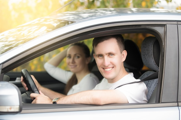 Jonge lachende man rijden en vrouw zitten in de auto