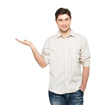 Jonge lachende man toont iets op palm geïsoleerd op een witte muur.