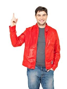 Jonge lachende man wijst met vinger omhoog in rode jas geïsoleerd op wit.