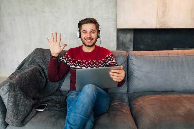 Jonge lachende man zit thuis in de winter, zwaaiende hand, hallo zeggen, rode trui dragen, bezig met laptop, freelancer, koptelefoon luisteren, student online studeren, in de camera kijken