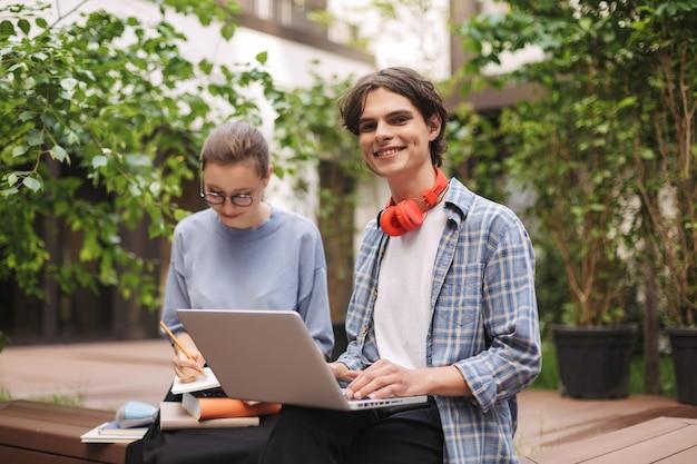 Jonge lachende man zittend op een bankje met laptop en gelukkig