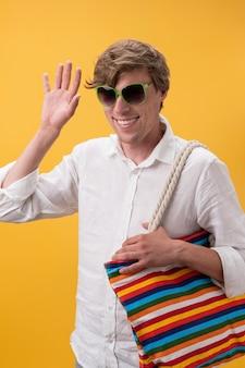 Jonge lachende man zwaait met zijn hand in de begroeting. glamour man met krullend haar in glazen en kleurrijke tas dragen witte overhemd glimlachend terwijl hij verblijft op gele muur.