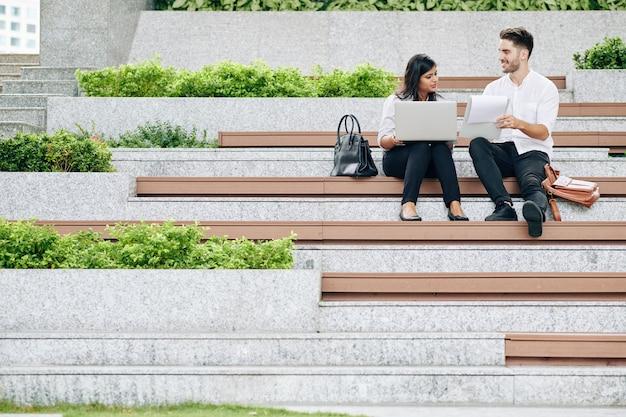 Jonge lachende managers buiten zitten, statistieken en projectdetails bespreken