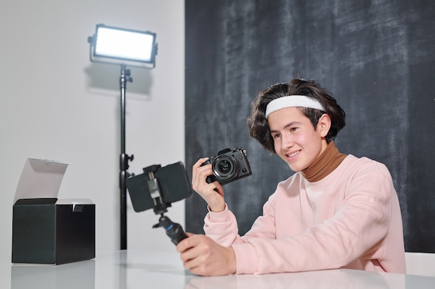 Jonge lachende mannelijke vlogger met fotocamera zit door bureau en zichzelf schieten op smartphone in studio