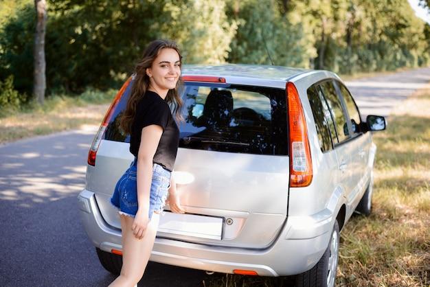 Jonge lachende meisje kofferbak openen. de vrouwelijke bestuurder hield auto dichtbij weg op platteland tegen en probeert bagageruimte te openen om iets te nemen