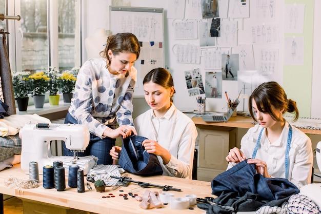 Jonge lachende modeontwerper poseren met een schaar op de werkplek en camera kijken terwijl twee mooie naaisters zitten aan de tafel en naaien in het werkproces